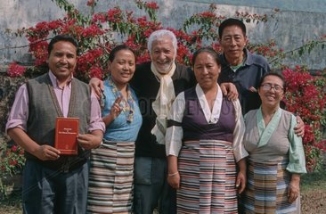 Man surrounded by Tibetan teachers at refuge camp