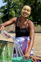Woman wearing a facial mask at the wellhead Madagascar