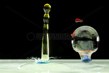 Drops of colored water and soap bubble on black background