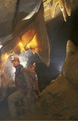 Speleologist in a subterranean flow under mineral draperies