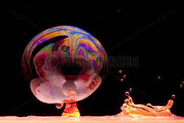 Drop of colored water and soap bubble on black background