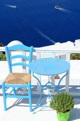 Table and chair and Aegean Sea in background. Greek Atmosphere  Santorini Island  Cyclades  Greece