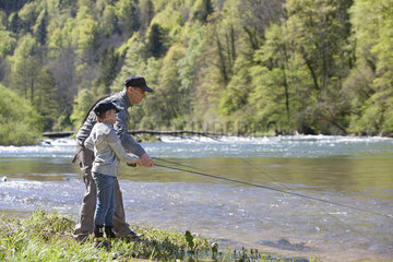Fly fisherman and child learning  River Doubs  Goumois  Franche-Comte  France
