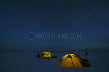Lit tents at night - Agardbukta Spitzberg