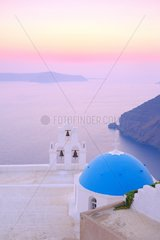 Chapel of Agiou Stylianou at sunset  with its blue dome and bell tower with 3 bells  this chapel is probably the most photographed of the Cyclades  Santorini Greece
