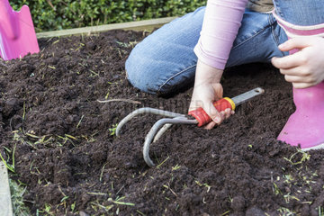 Young girl loosening the soil of the garden with a cultivator