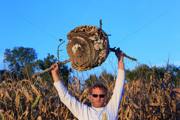 Portrait of Etienne Roumailhac  42 years old  hunter of Asian hornets  with an Asian hornets' nest. The nest's size can reach one meter in diameter and the population can exceed 20 000 hornets. France