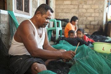 Man repairing fishnet - Lamahala Adonara Island Indonesie