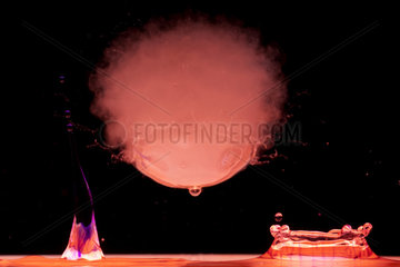 Drops of colored water and soap bubble filled with smoke on black background