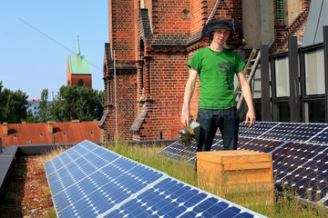 Urban Beekeeping - Philipp Markert  26 years old  with his hives on the Church of the Resurrection steps from Alexanderplatz and Karl Marx Avenue. Following the fall of the Wall  the church was transformed  into an environmental conference center with a vegetal roof and solar panels to produce electricity. ?I work as the head cook in a restaurant and I also studied to be an engineer in wood technologies at university? I started beekeeping two years ago after a seminar on bees. I hate pesticides and I shop for organic products at the local markets. It?s hard to be an ecological activist in Germany so I defend traditions  good cooking and organic products and I boycott supermarkets and the food industry that uses pesticides.? Germany