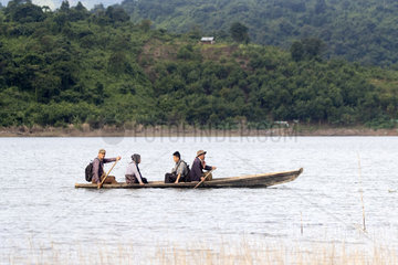 Boat on the water with 4 people on board  Doyang Hydroelectric Dam  where up to one million birds : Amur falcon (Falco amurensis) concentrate on the road to their migration to southern Africa  Nagaland  India