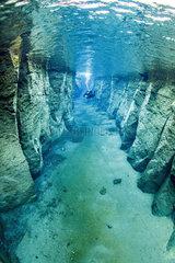 Scuba diver inside the volcanic crack Nesgjá  in the Ásbyrgi National Park  northern Iceland