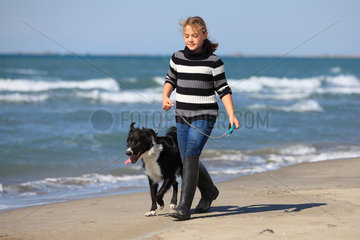 Girl playing with a Border Collie on a beach