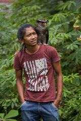 Barred eagle-owl also called the Malay eagle-owl (Bubo sumatranus) and his keeper  Harau Valley  Sumatra  Indonesia