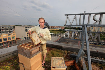 Urban Beekeeping - Andreas Krueger  42 years old  has set up his hives to the east  on the roof of the Hellersdorfer town hall on Alice Salomon square. Married with two children  he works as an instructor in an institution for the handicapped. He started beekeeping six years ago to satisfy an old childhood desire and to get back to nature. ?I also really wanted to make honey. I have a slogan  Honey before dogs?? He recounts that in Berlin it?s better to have bees than a dog because the bees make it a good environment. ?Otherwise  I run marathons. I have ten hives and tomorrow I am going to harvest the honey from the hives on the Hellersdorfer town hall and I hope to get 80 kilos per hive?. Germany