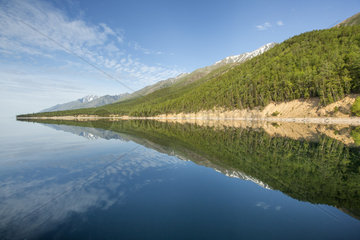 West coast shore with mountain and forest reflecting in the Lake Baikal  Siberia  Russia