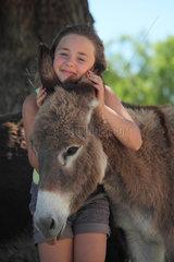 Little girl cuddling a Donkey