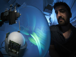 Apidologie - Alexis Buatois observes a new virtual system of visual learning for the bees. The bees are suspended in the locomotion compensator conceived for the analysis of their visual orientation. The bee  immobilized by the thorax  is placed on a hollow sphere of which the movements  induced by the walking of the bee  are recorded by optical sensors that allow for the reconstruction of the bee's trajectory. The bee walking on the compensator is exposed to visual stimuli present inside a cylindrical arena. The CRCA has shown that the cognitive capacities of recognition of visual forms by domestic bees are similar to those of humans and primates. This work was published in the revue Nature 2004. CNRS. Universite Paul Sabatier. Toulouse.