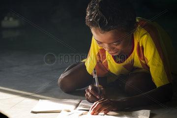 Child doing homework - Grogos Island Maluku Indonesia