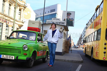 Urban Beekeeping - Erica Mayr  37 years old  posing with a Trabant  a hive and a smoker in front of Checkpoint Charlie. This young woman got the media buzzing when she placed her first hives on the roof of a warehouse in Berlin. Beekeeper since only 3 years ago  Erica is the owner of a trendy bar in the Kreuzberg neighborhood. Today  Erica is happy  because the bees and beekeeping are in line with her profession and university education as a landscaper and horticulturist.