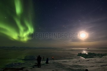 Photographing and filming aurora borealis. Background: the Scoresbysund  Greenland  February 2016