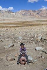 Boy playing riding a gas cylinder  Surroundings of Korzok  Leh  Ladakh  Himalayas  India