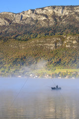 Fisherman in the morning mist on Lake Annecy in autumn  Haute Savoie  Alps  France