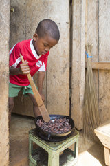 7 year old boy roasting cocoa beans in a pan  Santana  Sao Tome and Principe Island