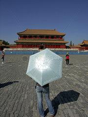 Young woman protecting herself with an umbrella Pekin