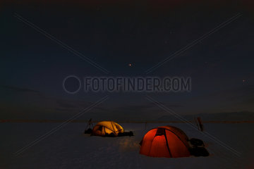 Lit tents at night - Agardbukta Spitzberg