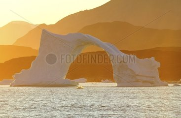 Denmark. Greenland. West coast. Sunset on an arch shaped iceberg in the straight of Vaigat  near the village of Saqqaq.