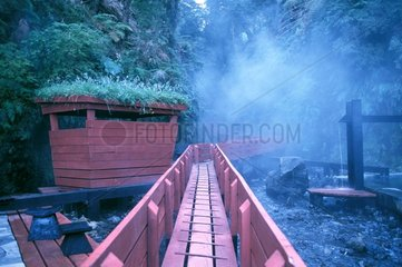 Footbridge and shed out of red wood in Termas geometricas