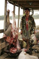 Travelling butcher on a boat Beni area Bolivia