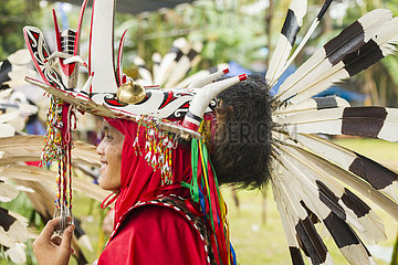 Man wearing mask and feather hornbill during Parade Hudoq
