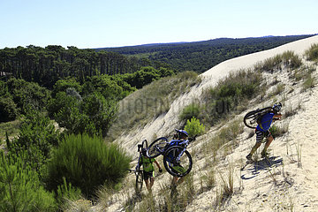 Cyclists carrying their ATV on the Dune du Pilat - France