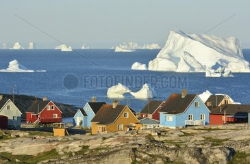 Denmark. Greenland. West coast. Disko Island. Houses of the village of Qeqertarsuaq with icebergs on the foreground.