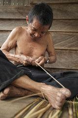 Man weaving a traditional fish basket - Borneo Indonesia