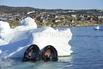 Denmark. Greenland. West coast. Zodiacs pushing an iceberg to free the entrance of the harbour of Ilulissat.