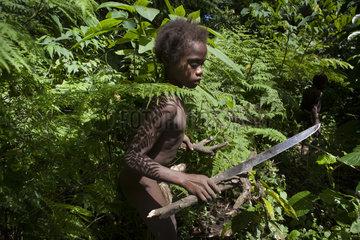 Boy opening a path in the forest - Tanna Vanuatu