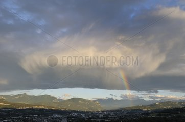 Cumulus clouds and rain under rainbow sky above Chambéry