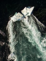 Aerial view of iceberg grounded in shallow rapids during tidal rip in Wager Bay on summer morning  Ukkusiksalik National Park  Nunavut Territory  Canada