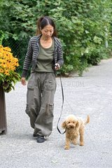 Woman walking with a miniature poodle bitch in a garden