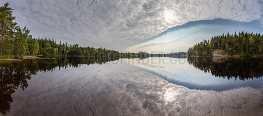 Perfect reflection in Sandsjoen lake  in south-west Sweden at the end of summer.