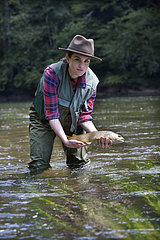 Young woman presenting a wild Trout of the Doubs (Salmo trutta fario)  Fly fishermen on the French-Swiss Doubs river  La Goule  Franche-Comte  France