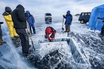Cutting a hole in the ice before a dive - Lake Baikal  Siberia  Russia