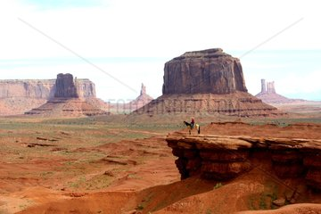 Navajo rider on rock overhang - Monument Valley Utah