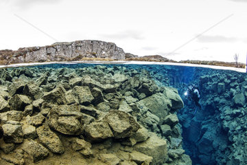 Diver explores the Silfra Hall a part of the crack that leads to the cathedral  part of Silfra fissure  deep fault filled with fresh water in the rift valley between the Eurasian and American tectonic plates. Silfra fissure is actually a crack between the North American and Eurasian continents that drift apart about 2cm per year. Thingvellir National Park  Iceland.