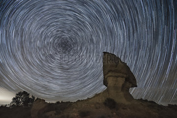 Rock formation in Los Monegros area in front of star trails during a clear february night  Aragon  Spain