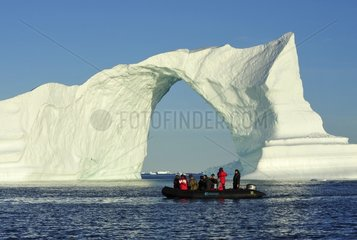 Denmark. Greenland. West coast. Zodiac near an arch shaped iceberg in the straight of Vaigat.