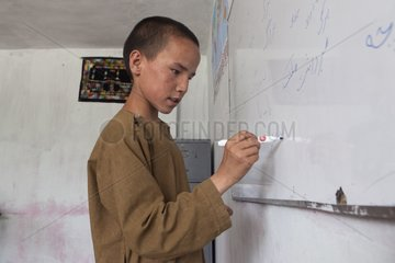 Schoolboy writing in a mixed school - Kabul Afghanistan